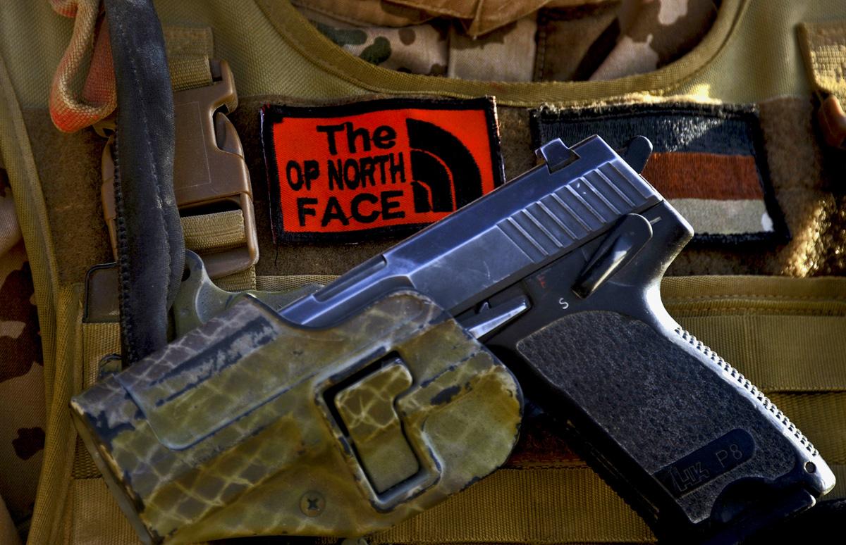 """Ein Soldat trägt im OP-North neben einer Pistole P8 von Heckler und Koch einen Aufnäher mit der Aufschrift """"The OP NORTH FACE""""."""