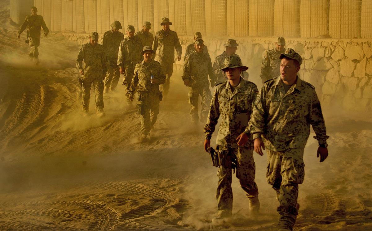 Soldaten gehen im OP North einen staubigen Weg entlang.