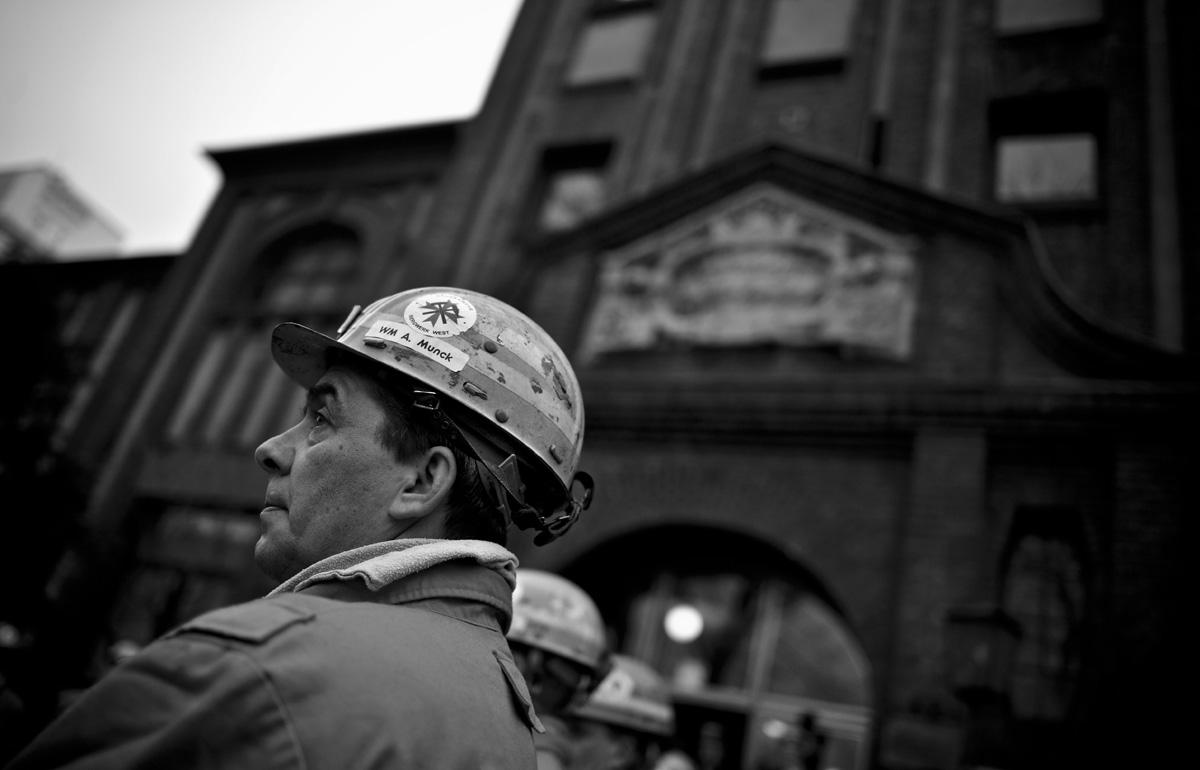 Ein Bergmann steht im Rahmen der Fördereinstellung vor dem Eingang zur Lohnhalle des Bergwerk West.